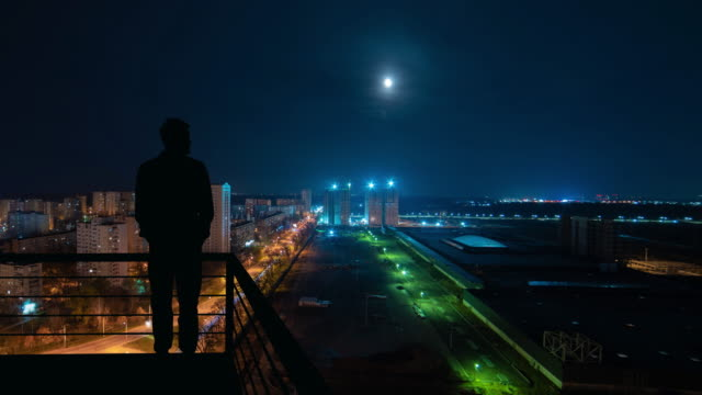 the man stands on the top of building on the night cityscape background - man look sky scraper video stock e b–roll