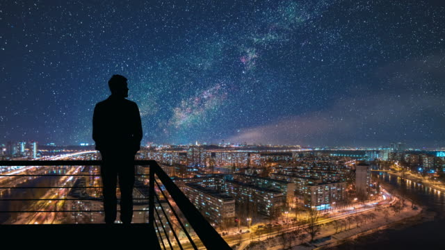 the man stands on the top of building on the starry cityscape background - luce stradale video stock e b–roll