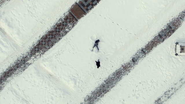 The man throws a snowball in his friend during the guy makes angel on snow video