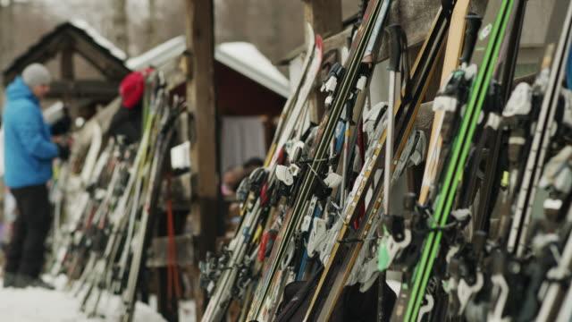 the man took the skis in the winter resort stock video - negozio sci video stock e b–roll