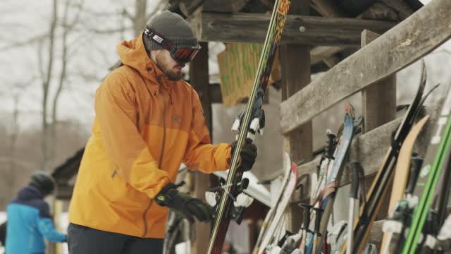 l'uomo ha preso gli sci nel video stock della località invernale - negozio sci video stock e b–roll