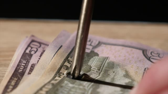 The man twists the screws into the money using a screwdriver The man twists the screws into the money using a screwdriver. power tool stock videos & royalty-free footage