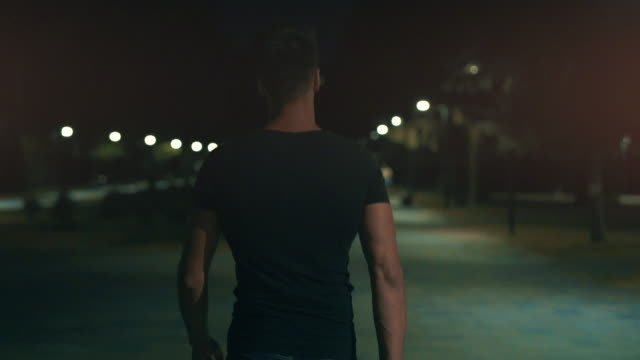 The man walking in the night park. slow motion