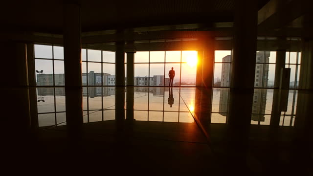 the man walking in the office center on a bright sun background. slow motion - man look sky scraper video stock e b–roll