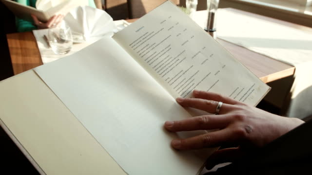 The man watches the menu at restaurant of hotel The man thumbs through the menu at restaurant of hotel and looks for a desirable dish menu stock videos & royalty-free footage