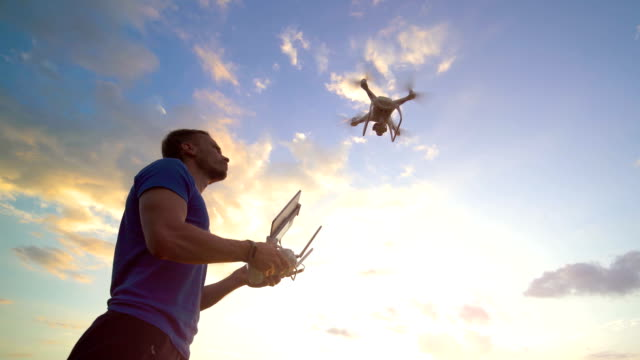 the man with a controller launching a quadrocopter in the sky - telecomando background video stock e b–roll