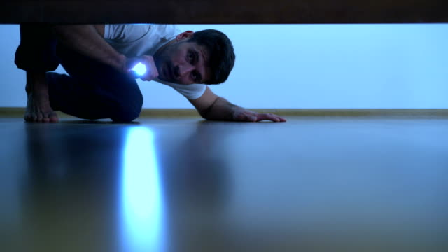 The man with a flashlight looking under the bed. evening night time