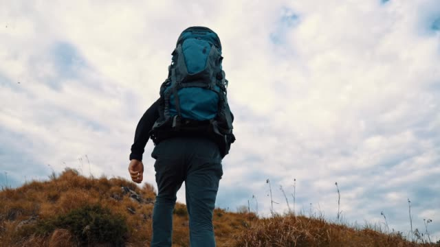 The man with backpack walking to the top of a mountain