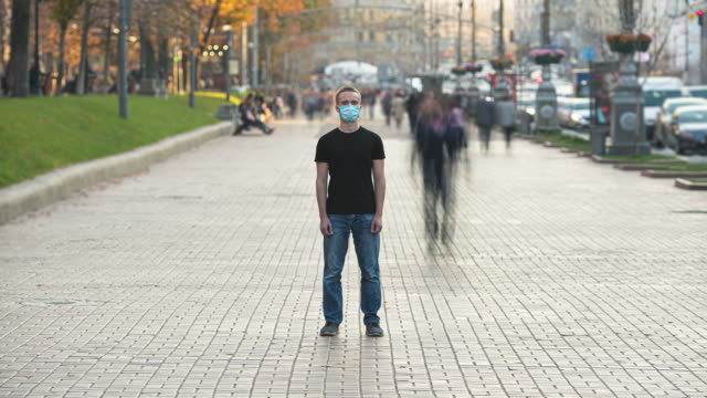 vídeos de stock e filmes b-roll de the man with medical face mask stands in the crowded city. time lapse - isolado