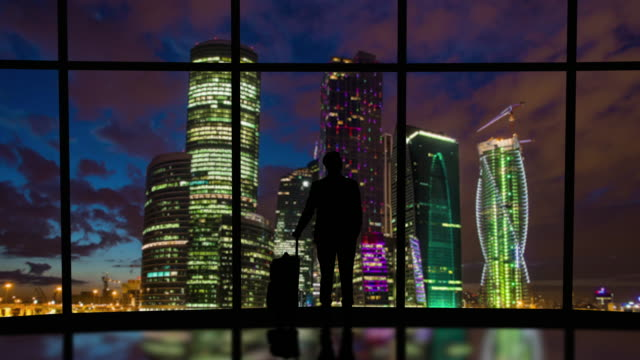 the man with suitcase stands near the window on night city background. time lapse - man look sky scraper video stock e b–roll