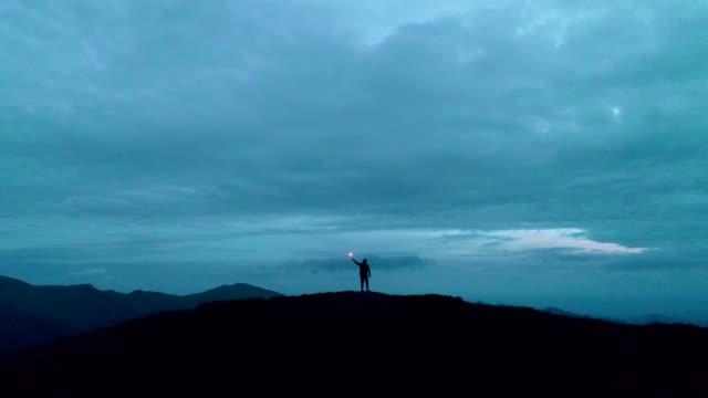 밤 산에 서 있는 불꽃놀이 막대기를 가진 남자 - mountain top 스톡 비디오 및 b-롤 화면