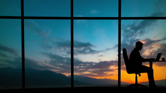 The man working near a panoramic window on a mountain sunset background