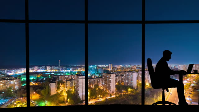the man working near a panoramic window on a night city background. time lapse - man look sky scraper video stock e b–roll