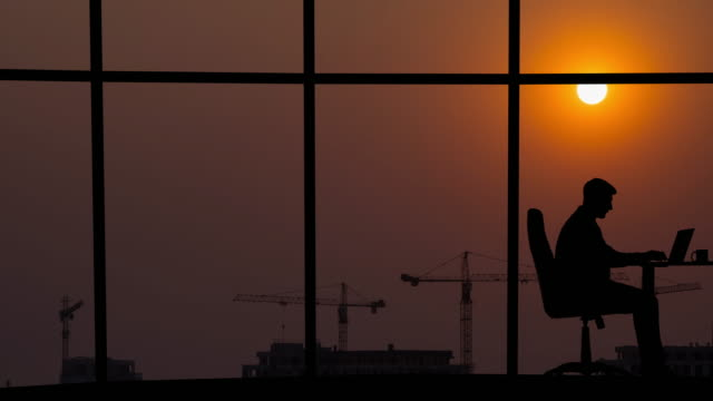 The man working near a panoramic window on a sunset background