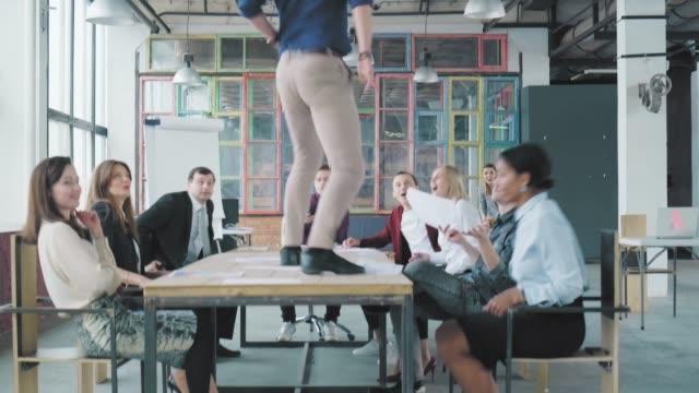 支配人はテーブルの上に立ち上がり、踊り始める。従業員は彼と一緒に踊り、成功を祝います。企業関係者。オフィスライフ。労働者は祝う。コワーキング ビデオ
