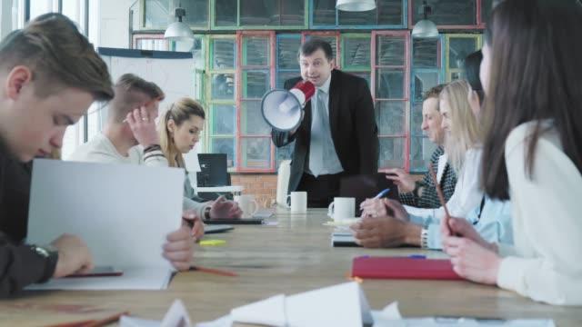 ビジネススーツを着たマネージャーは椅子から立ち上がり、メガホンを手に持ち、スタッフに向けて誓い、叫ぶ。そのビジネスチームは機嫌が悪い。オフィスライフ。クリエイティブなイン� ビデオ