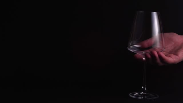 the man's hand puts an empty glass for wine on a black background and shaves it off. isolated static shot. serving a luxury dinner, the concept of winemaking and alcohol tasting 4k - bicchiere vuoto video stock e b–roll