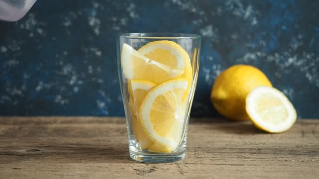 the man's hand slowly pours fresh clean water from the jug into a glass with slices of lemon. lemonade on wooden table and blue background. living water, healthy drink - лимон стоковые видео и кадры b-roll