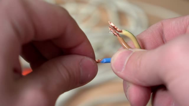The man's hand twists the copper wires