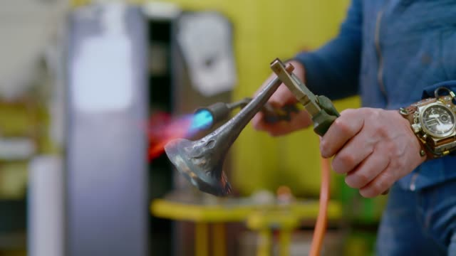 stockvideo's en b-roll-footage met de handarbeiders die-omhoog het koper detail met de gas-toorts verwarmen - metaalbewerking