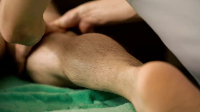 The masseur doing sports friction and massage of legs for sportsman The masseur doing sports friction and massage of legs for sportsman. FullHD human back stock videos & royalty-free footage