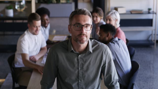 The master at facilitating productive meetings 4k video footage of a confident mature businessman working in a modern office with his colleagues in the background group of objects stock videos & royalty-free footage