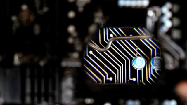 The master looks a components at motherboard under a magnifying glass video