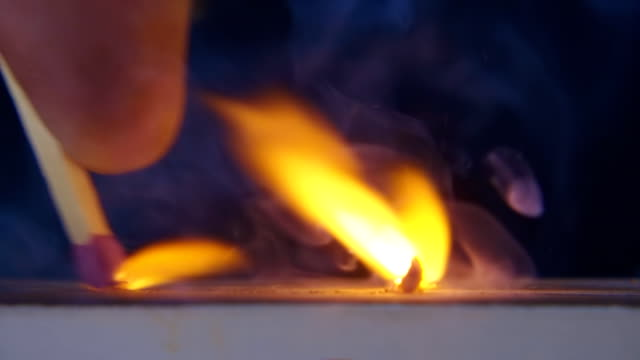 The match in the hand moves on the side of the matchbox and light the fire video