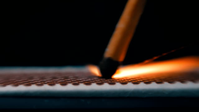 The match moves on the side of the matchbox and light the fire. Macro The match moves on the side of the matchbox and light the fire. Closeup. Shallow depth of field. Slow motion. Color correction igniting stock videos & royalty-free footage