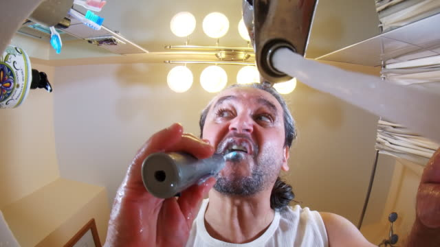 The mature, 45 years old, long-haired man brushing teeth. video