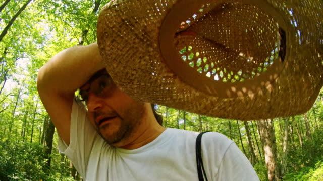 l'uomo maturo, di 45 anni, dai capelli lunghi che indossa il cappello di paglia, cammina nella foresta di poconos, in pennsylvania, in una calda giornata estiva soleggiata. - hickory run video stock e b–roll