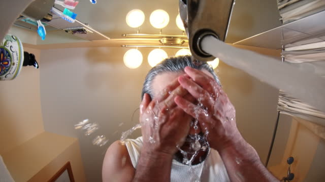 The mature, 45-years-old, long-haired, unshaven man washing the face and hands. video