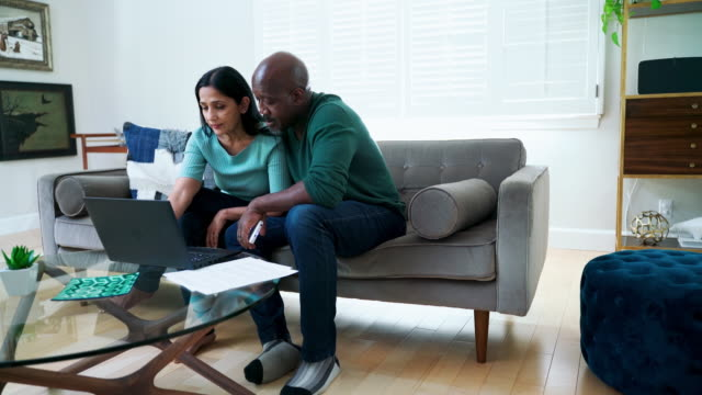 The mature couple sitting together on a couch and using a PC laptop for online shopping or video call via the internet. A mature couple of Latino people at home. Lifestyle - everyday life, 4K UHD video footage. 50 59 years stock videos & royalty-free footage