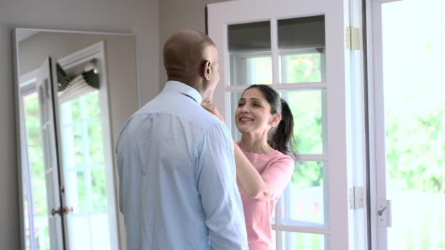vídeos y material grabado en eventos de stock de el hombre latino maduro preparándose para el trabajo, parado frente a una gran ventana en el dormitorio y ajustando una corbata. su esposa viene a ayudarlo. - corbata