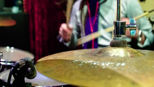 The mature man, drummer, playing in the live performance in the nightclub video