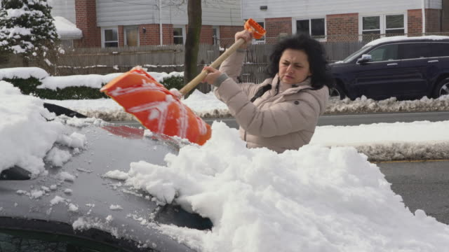 The mature woman cleaning the car from the snow after winter storm
