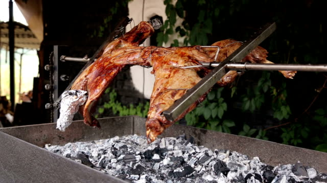 The meat is fried on a grill on a spit. video