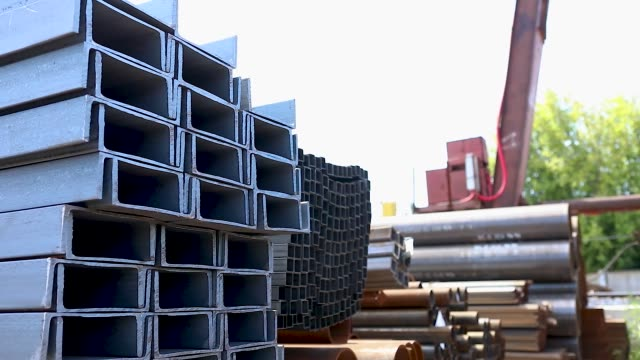 the metal channel laid in rows in the open metal warehouse, the large metal channel in the warehouse - acciaio video stock e b–roll