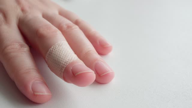 The middle finger of a woman's hand with a bodily adhesive bandage. video