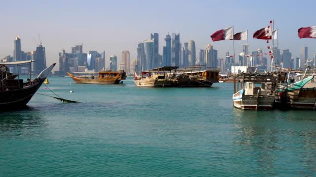 vidéos et rushes de le mélange des âges. vue sur les toits de la ville moderne de doha. journée tir, qatar, moyen-orient. bateaux traditionnels en bois qatar avec des drapeaux de qatar à corniche broadway côte dans de l'eau propre bleu azur du golfe persique. - doha
