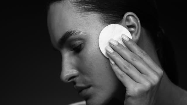 The model uses a cotton pad. Supermodel face closeup. Make-Up