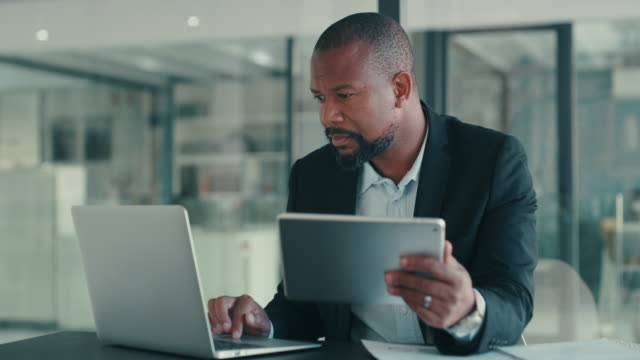 The modern businessman is nothing without his modern tools 4k video footage of a mature businessman using a digital tablet and laptop in an office businessman stock videos & royalty-free footage