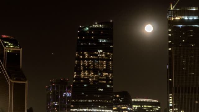 The moon rising over the illuminated highway and the night city, time lapse