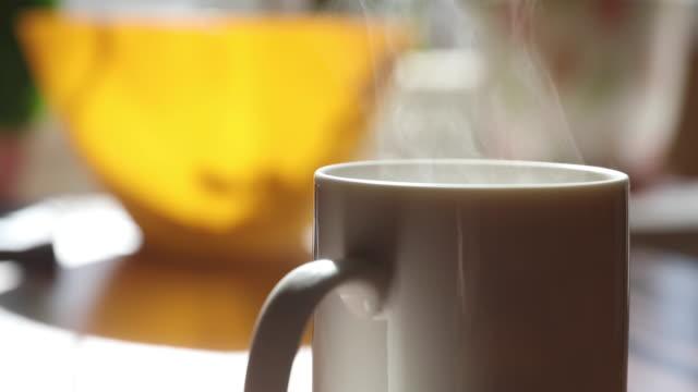 vidéos et rushes de la tasse du matin de café ou de thé dans une journée ensoleillée attend sur une table, boisson chaude, il y a de la vapeur qui est éclairée par le soleil d'une fenêtre, un fond de couleur vive, le soleil, une tasse de couleur blanche - boisson chaude