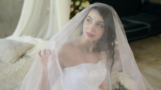 The morning of a gentle attractive brunette. Beautiful bride is smiling and looking out the window touching the veil while sitting on the bed. video