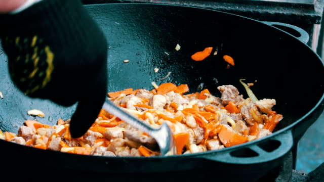 The most delicious Uzbek pilaf with carrots rice and meat is brewed in huge tub at the festival food court video