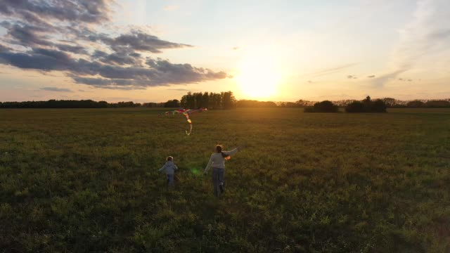 The mother and boy run with a kite on a green field. Laughter and joy, festive mood. Autumn,Sunset
