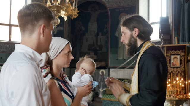 The mother kisses a cross during the ritual of baptizing of her son in church video