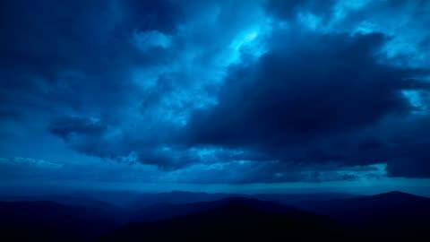 vidéos et rushes de le paysage de montagne sur le contexte de flux de nuage. soirée nocturne - ciel couvert