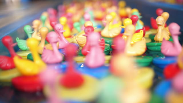 The multi colour plastic ducks floating on the water with lucky game
